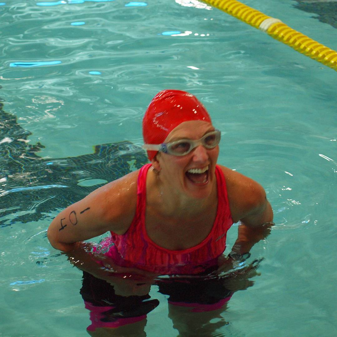 A woman in a pool wearing a pink one piece swimsuit and a red swimcap and goggles with her mouth wide with laughter.