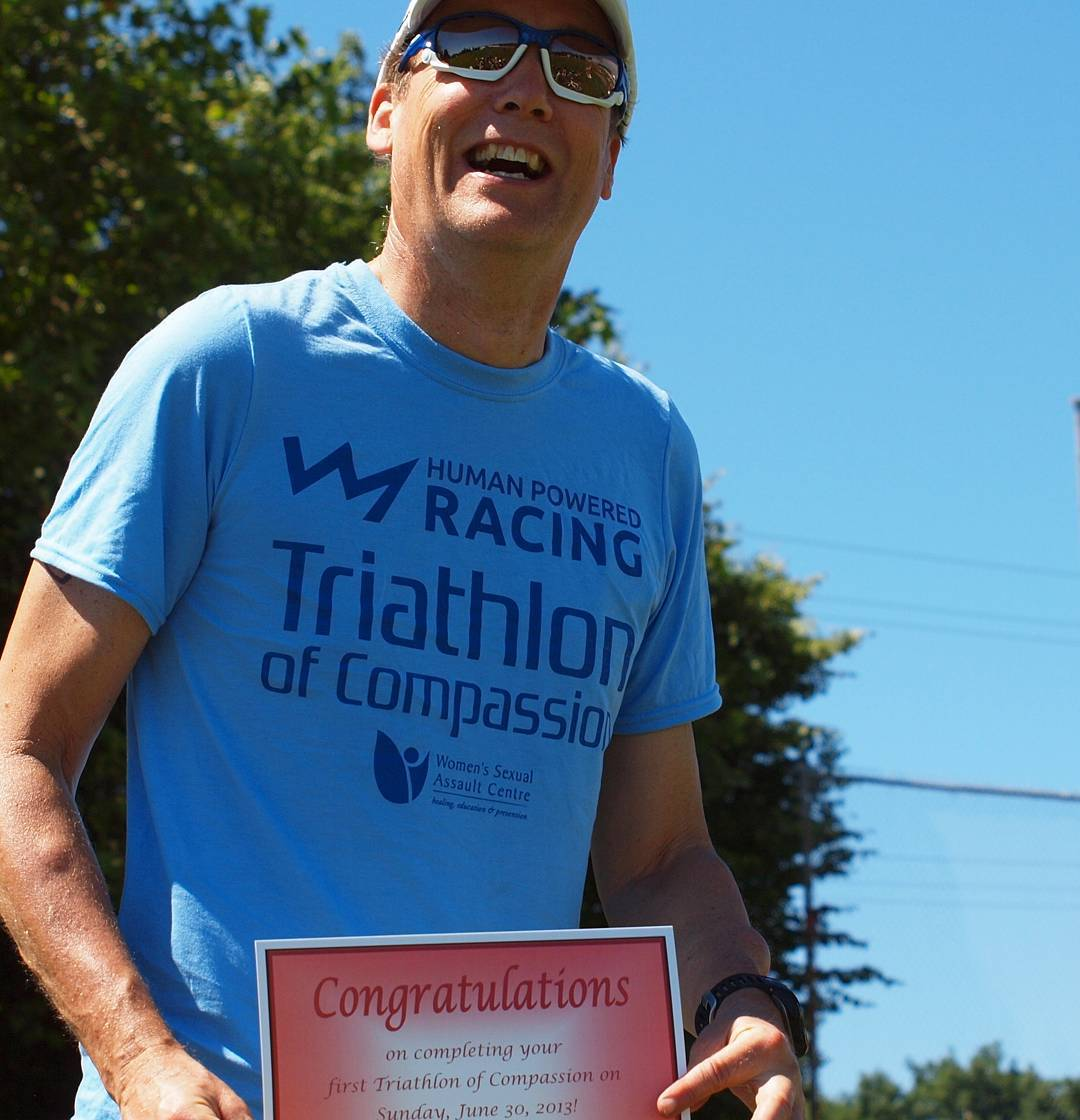 "A man in a blue tshirt that says ""Human Powered Racing Triathlon of Compassion"" and sunglasses is smiling and holding a red ""Congratulations on Completing your 1st Triathlon of Compassion"" certificate. There are trees behind his to the left and a clear blue sky in the background."