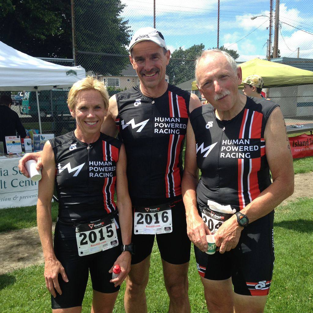 """Three athletes standing shoulder to shoulder in matching black red and white triathlon body suits that say """"Human Powered Racing"""" on them. They are all smiling. There are two men on the right and one woman on the left. They are standing in a green grass field. There is a white tent in the background to the left, and the sky is bright blue with white fluffy clouds."""