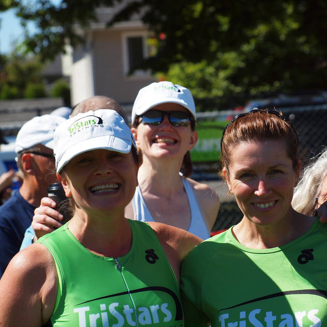 "Two women from the chest up wearing bright green tanks that say ""TriStars"" in white letters. Both are smiling, and they have their arms around each other. There are green trees, a house, and a blue sky in the background as well as a woman smiling behind the two in front, but the background is out of focus."