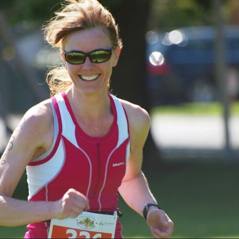 A woman in a pink tank top visible from the waist up is running. She is also wearing sunglasses and has a race number pinned to her stomach. She is smiling. It looks sunny with grass and trees in the background, but the background it very out of focus.