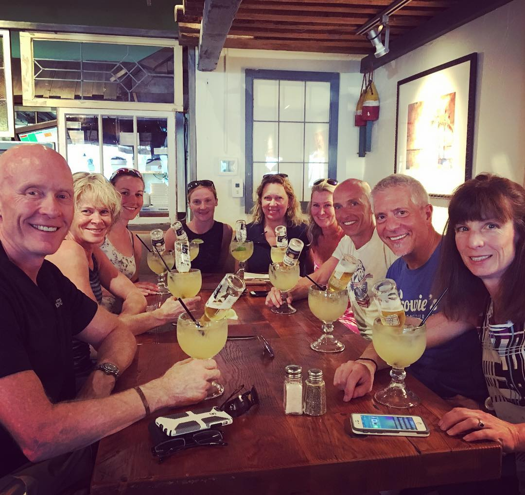 A group sitting around a long wooden table. It is a large group of about nine people, and they all have yellow margaritas in margarita glasses. All are smiling at the camera, which is positioned at the front of the table.