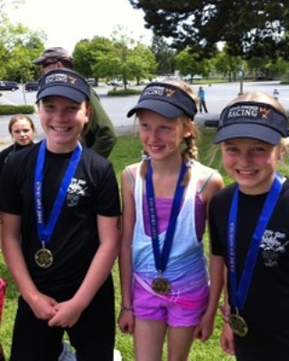 "Three young girls with medals on blue ribbons around their necks are standing shoulder to shoulder and smiling. They are all wearing running clothes and matching black ""Human Powered Racing"" visors. The back ground looks like field, and then a paved area, and then a patch of trees on a grey, but slightly sunny day. The background it out of focus."