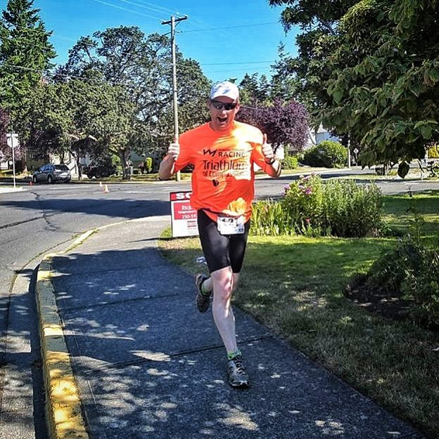 "A man running giving a double thumbs up and wearing an orange ""Human Powered Racing Triathlon of Compassion"" tshirt. He is running on a sidewalk with green grassy lawns and trees on either side of the road. It is a clear sunny day. He is smiling."