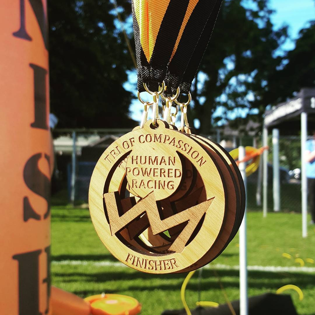 "Three wooden medals hanging on orange and black ribbon back to back so that we can only see the face of the one in front. It says ""Tri of Compassion"" at the top, ""Finisher"" at the bottom, and ""Human Powered Racing,"" in the middle above their logo, which looks like the silhouette of a jagged mountain range. Behind them is an out of focus field of green grass, and to the left is part of the inflatable orange finish line."