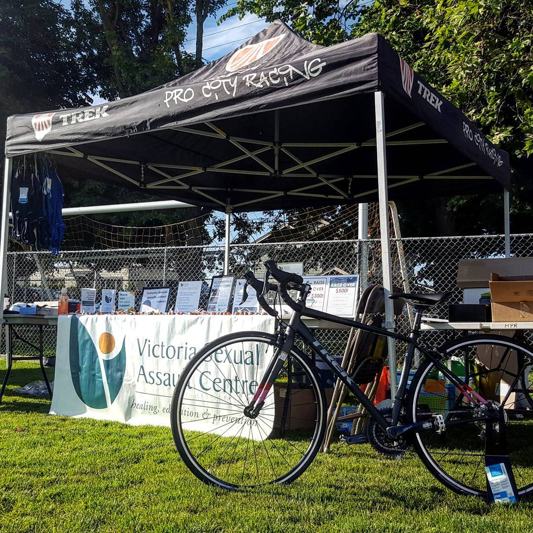 "A black tent that says ""Trek ProCity Racing"" on it has a sign beneath it for the ""Victoria Sexual Assault Centre,"" and to the right is a black bike leaning against the leg of the tent. All of this is on a green field with trees and a blue sky in the background."