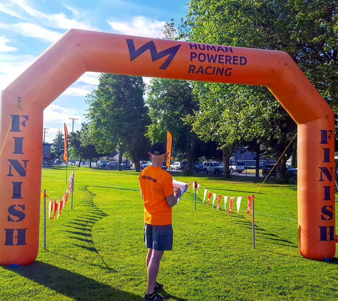"A man in an orange ""Human Powered Racing"" tshirt and black baseball cap standing in front of an inflatable orange ""Human Powered Racing"" finish and start line that is shaped like an archway. He is standing on a green grassy field with trees to the right. They sky is blue with white fluffy clouds."