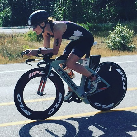 A woman biking. She is leaning low over her handle bars, dressed in black shorts, tank, and helmet. She is biking on a road with dry grass and some trees visible in the background.