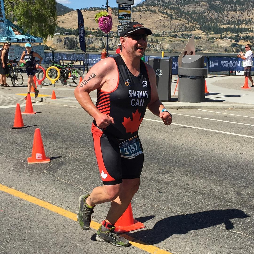 Photo of a man running on a road in a triathlon body suit that is black with red strips on the sides of his body and a red Canadian maple leaf on his stomach. He is also in a black baseball cap. There are orange cones behind him, and in the distance are dry grassy hills.