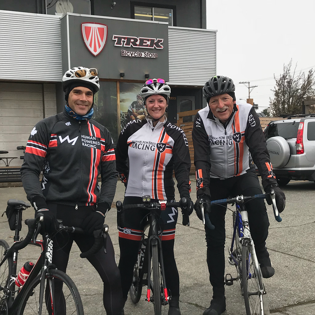 """Three bikers in their gear with their bikes. Behind them on the left is a grey store with metal siding and the sign reads """"Trek."""" It is a grey cloudy day."""