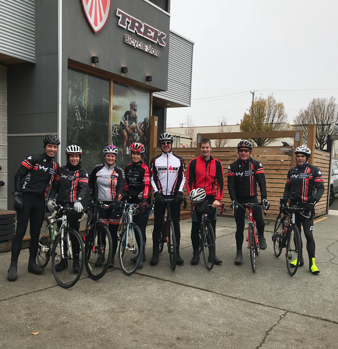 "This is a group photo of bikers in their gear with their bikes. Behind them on the left is a grey store with metal siding and the sign reads ""Trek."" It is a grey cloudy day."