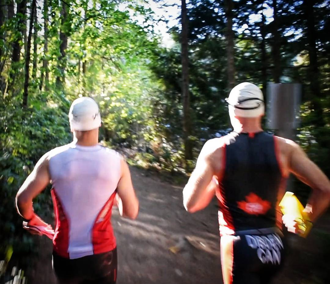 Two people running down a trail with evergreen trees on either side facing away from the camera. Both are wearing triathlon bodysuits and swim caps. It is a sunny day.