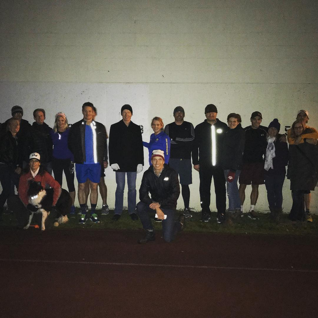 A group of people standing and sitting in front of a white wall at night in running gear. There is also a black and white boarder collie being snuggled in the bottom left.