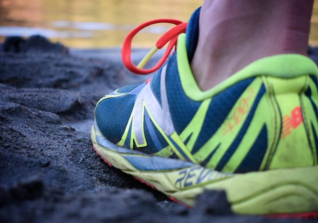 A close up of a NewBalance running shoe. It is green and blue with red laces, and we can only see the ankle of the wearer. The shoe is on wet rock and there is water visible in the background.