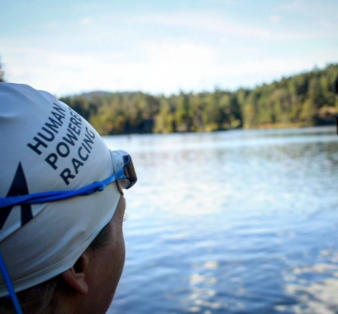 "In the left is a person wearing a white ""Human Powered Racing"" swim cap. They are the part of the photo in focus. We cannot see their face because they are looking away from the camera and out across a lake with evergreen trees on the other side. They are also wearing blue goggle, which are pushed up on the swim cap in the photo."