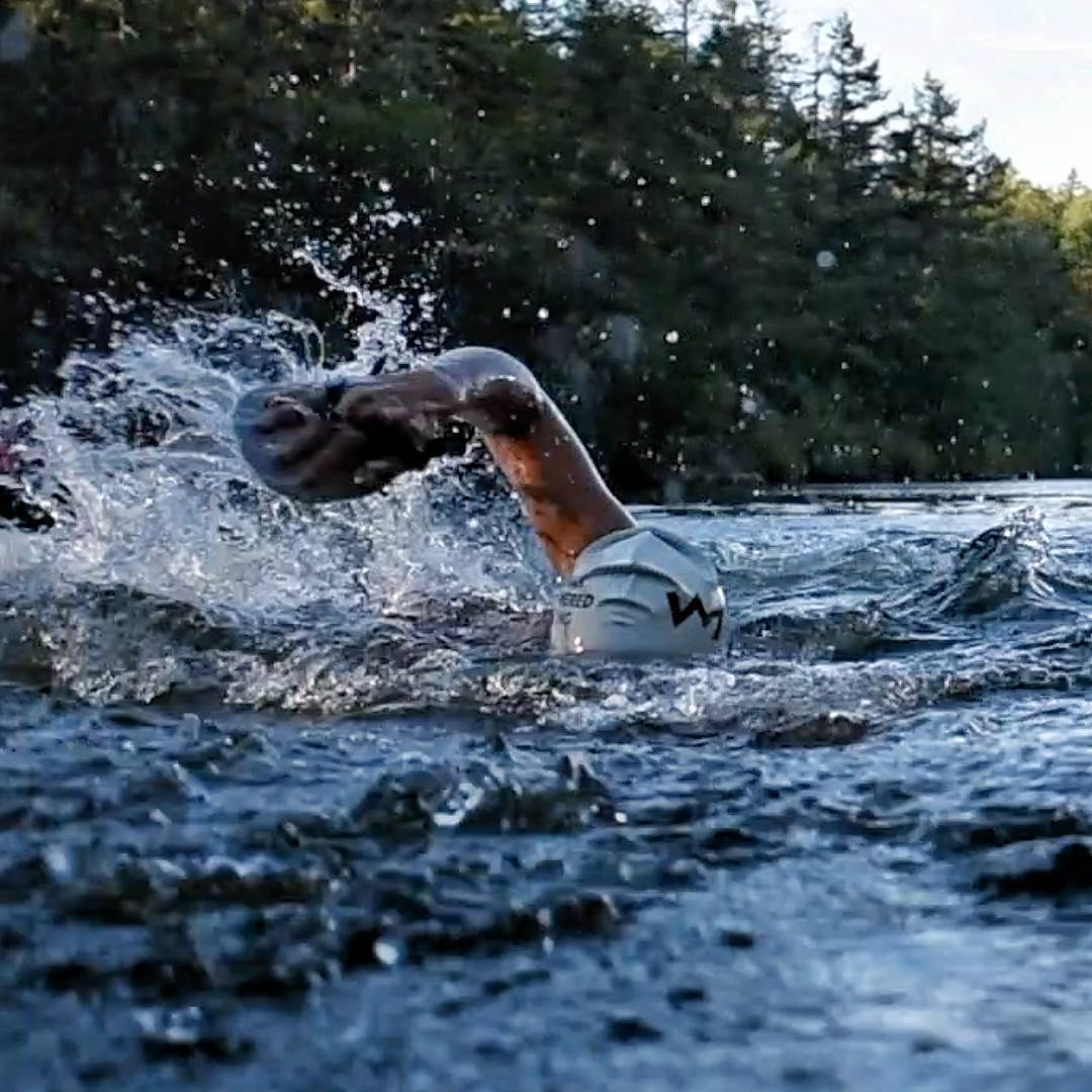 This photo is taken as though the camera is just above the water, and there is a person swimming towards the photographer. Only the swimmer's white HPR swim cap and their right arm, which is reaching forwards in front crawl with a black fin like glove, are visible above the water. There are evergreen trees in the background on the shore.