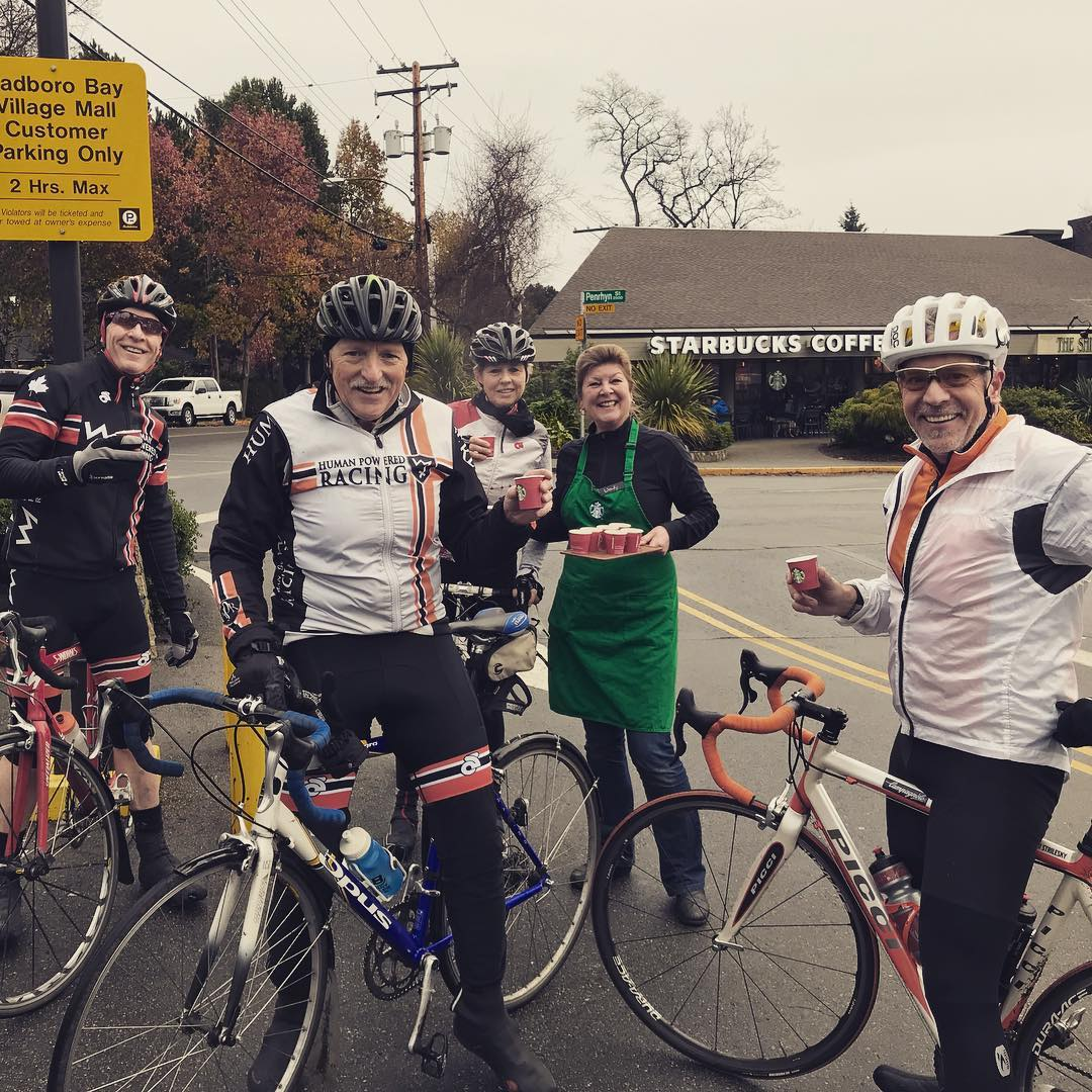 Three men and one woman on bikes in biking gear and helmets outside a starbucks smiling with another woman who is wearing a starbucks green apron. The women have their arms around each other. It is a grey day.