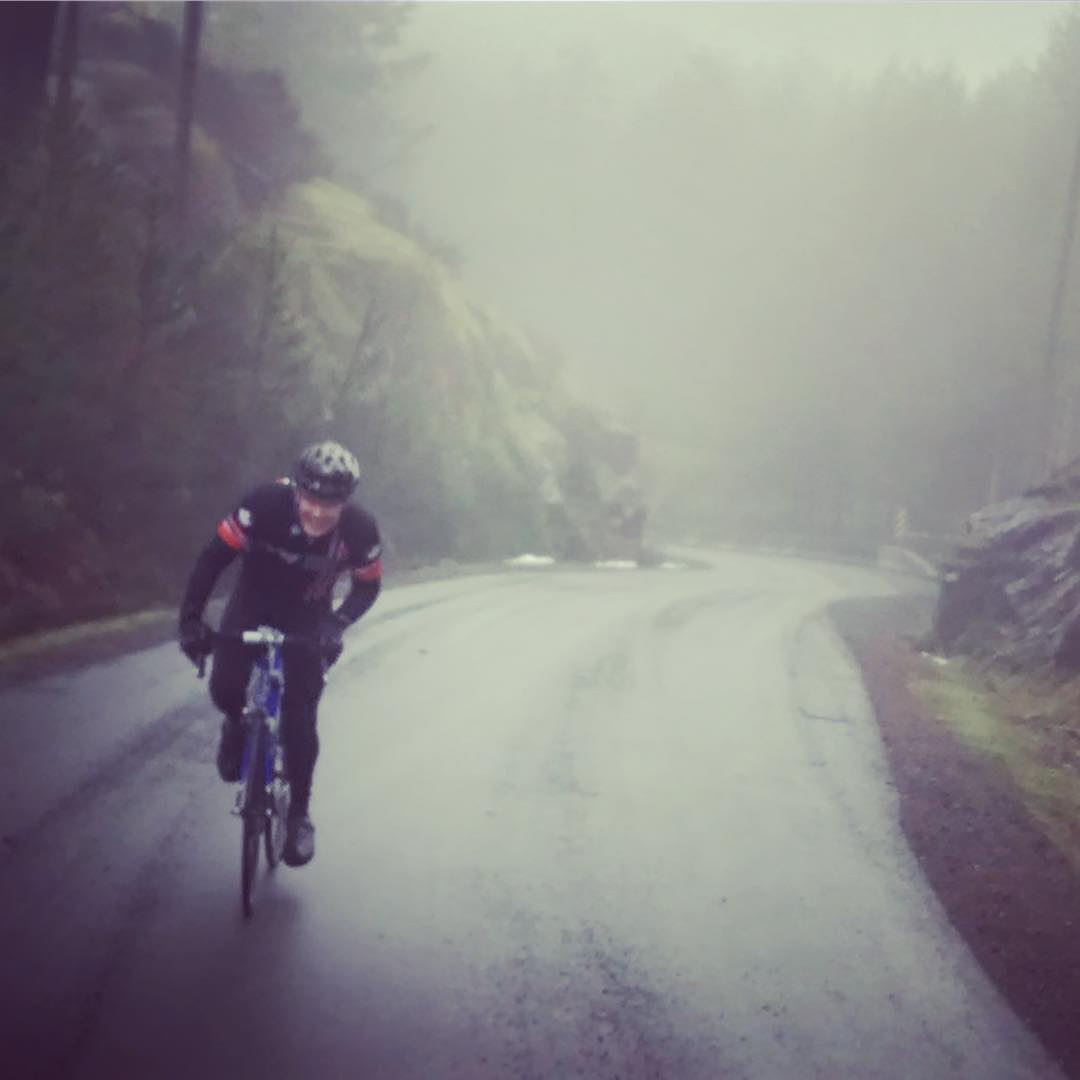 A woman biking on a road through thick fog. She is to the left of the photo and there are mossy rocks on either side of the road.