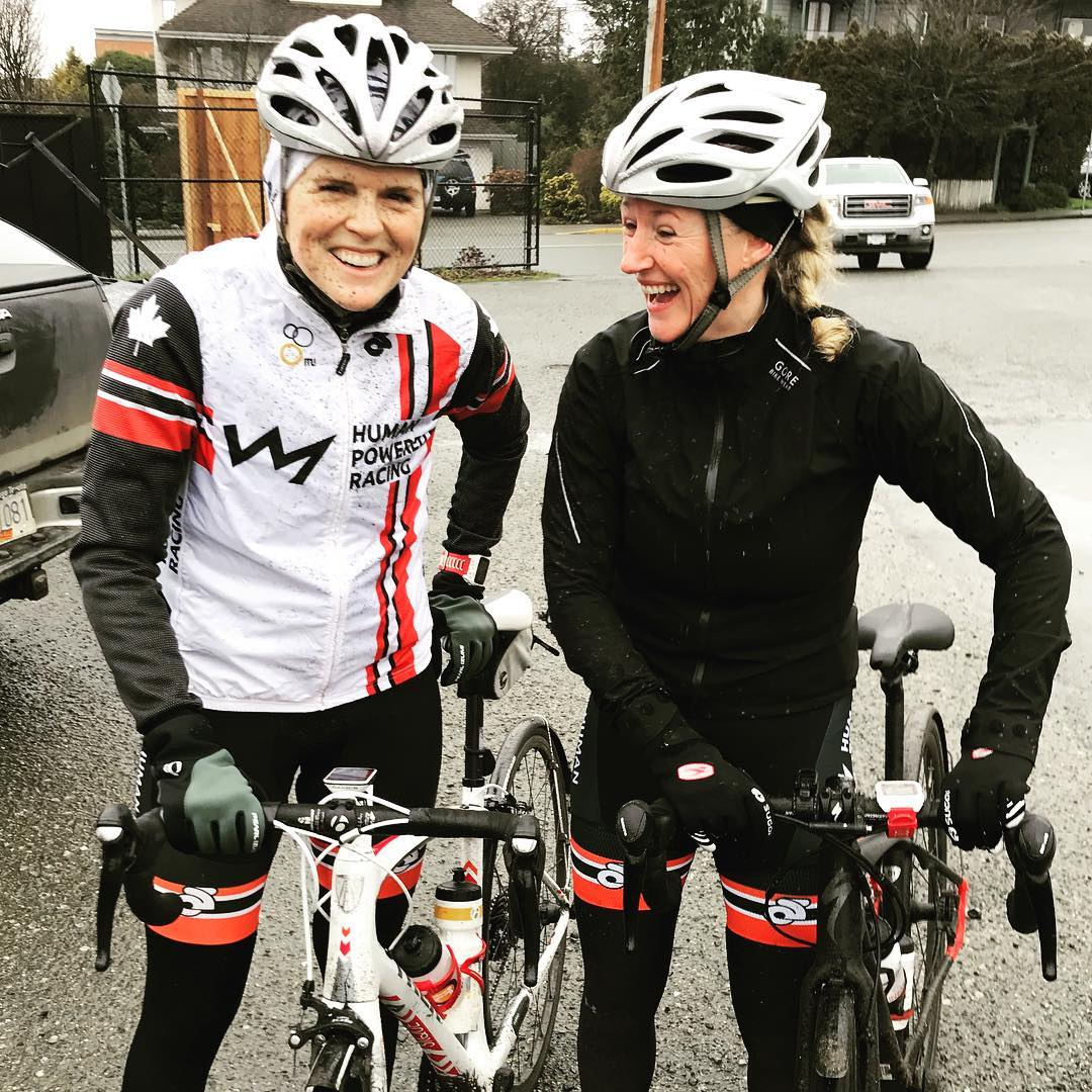Two women standing beside their bikes and smiling. Both have white helmets and look very damp.