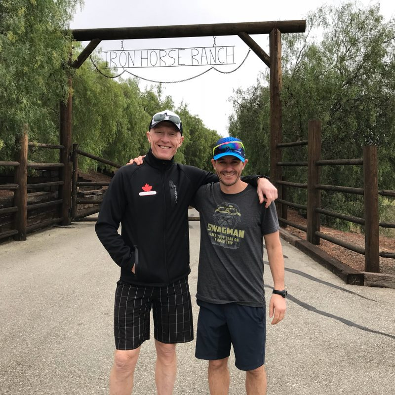 This is a photo of two men in shorts standing smiling with their arms around each other. They are outdoors, and in the distance are trees and a wooden archway with two vertical posts supporting a horizontal post on top.