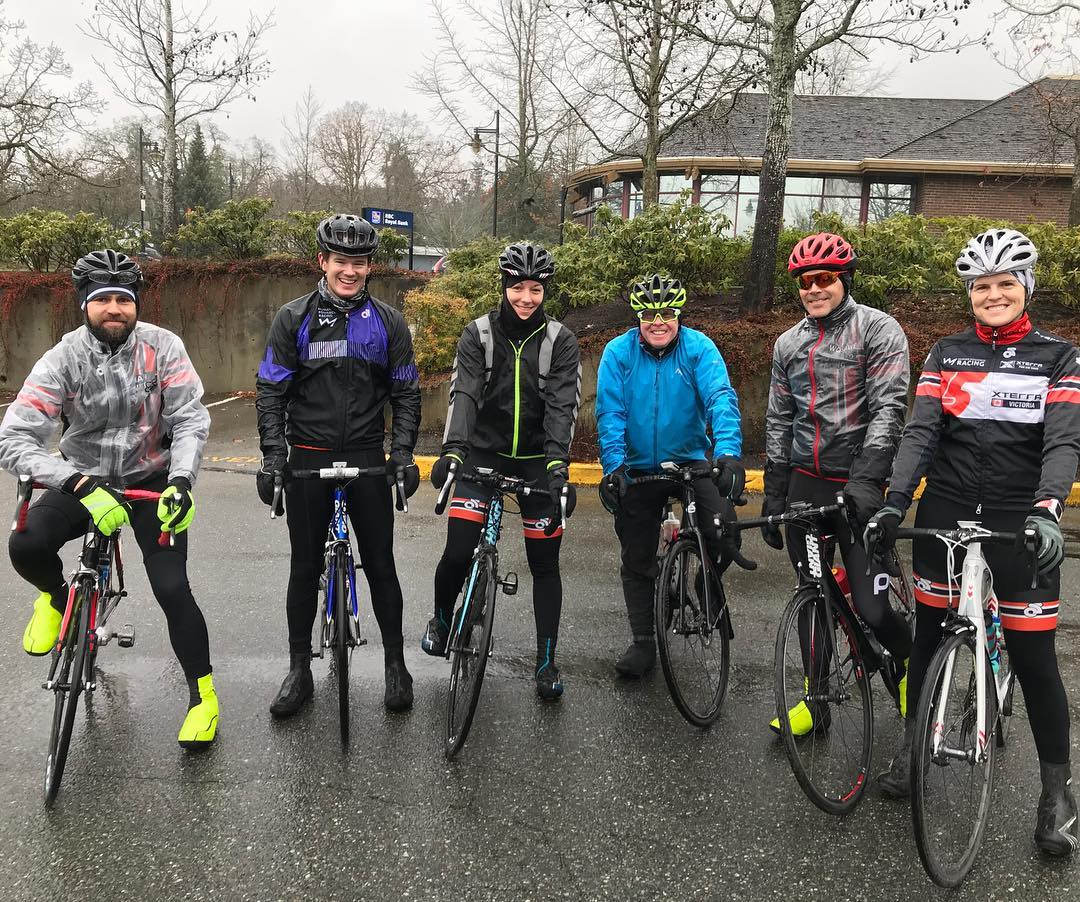 A group of six bikers sitting on their bikes and smiling at the camera. They are very damp and it is a grey, rainy day.