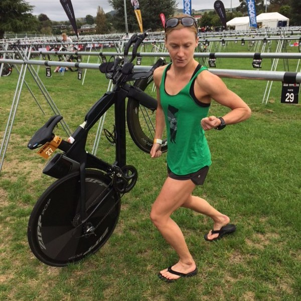 A ginger haired woman beside a black exercise machine standing on the grass. She is very muscular and flexing her right arm at the camera.