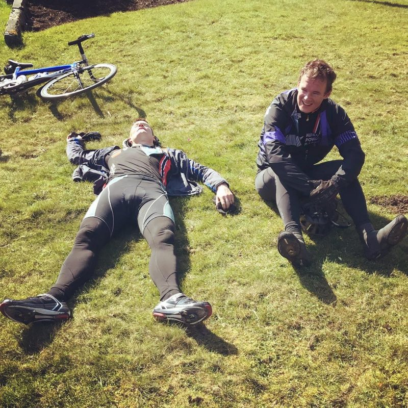 This is a photo of two men in black biking outfits on the grass. One is lying down and the other is sitting, legs outstretched, beside him.