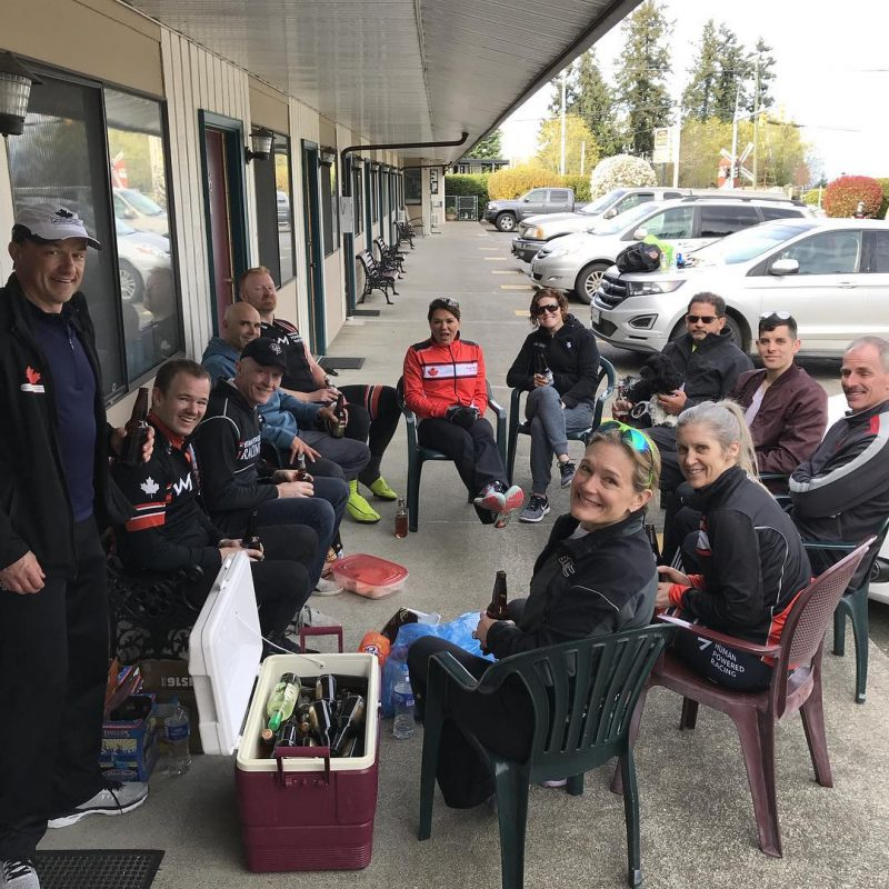 This is a group of people sitting in lawn chairs in a parking lot with a cooler of beer. They are smiling up at the camera in sporty gear.