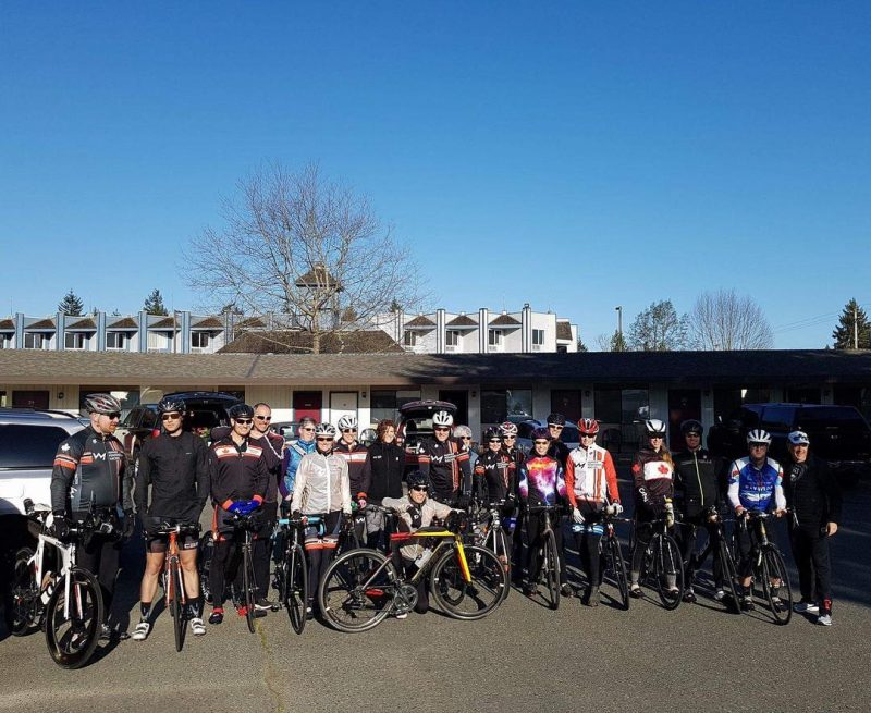 This is a group photo of bikers standing out front of a long one storey building under a clear blue sky.