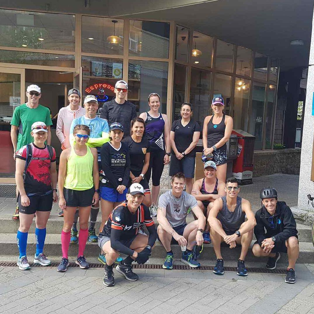 Group of people in running gear standing outside of a class building with wooden frames for the floor to ceiling windows. They are outside but you cannot see the sky because of the building behind them.