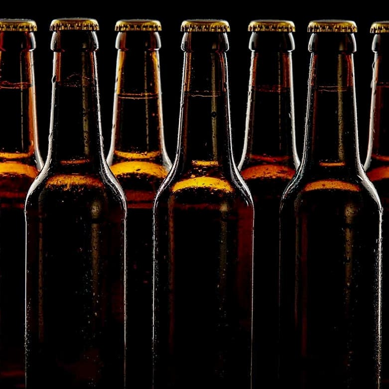 Seven beer bottles without labels against a black background with some light coming through from an unknown source. The bottles look brown in the light shining through them.