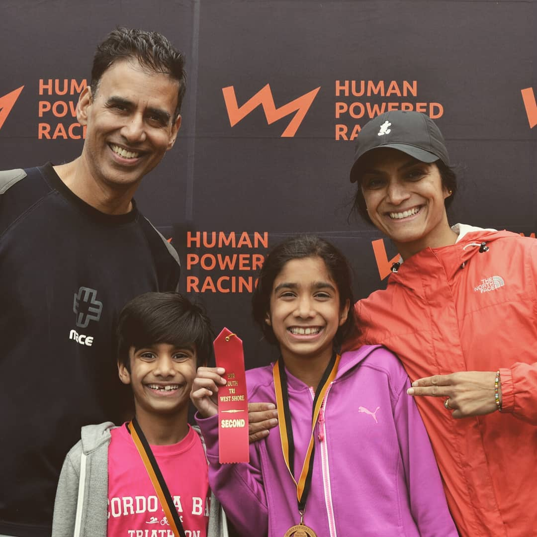 This is a photo of a family of four with a mother, father, daughter, and son. They are standing against a backdrop of the HPR logo, which is an orange line that looks a bit like the outline of a mountain range. They are all in fitness gear, and the children have wooden metals around their necks.