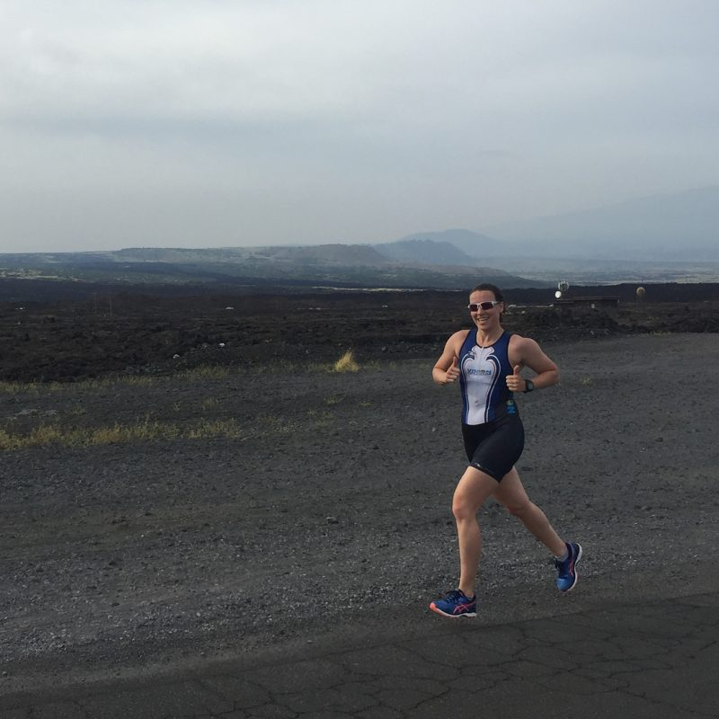 This is a photo of a woman running along a gravel road in a triathlon body suite on a grey day with low mountains in the background.