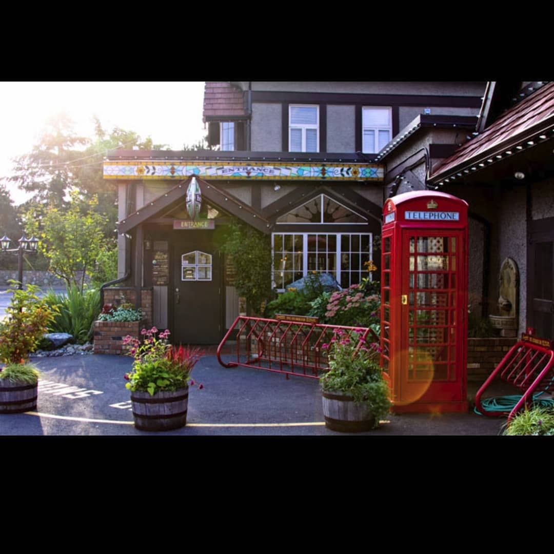 The outside of Six Mile Pub on a sunny day. It looks like a Tudor style cottage, and has a red British telephone booth out front which is on the right in this photo.