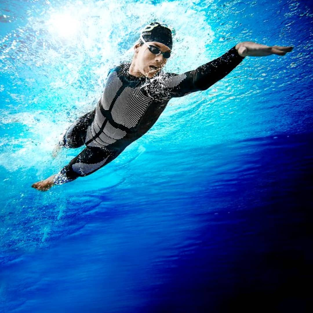A view from underneath a swimmer doing front crawl in a black and grey full body wetsuit with goggles and a swim cap on. There is light shining through the water above the swimmer.