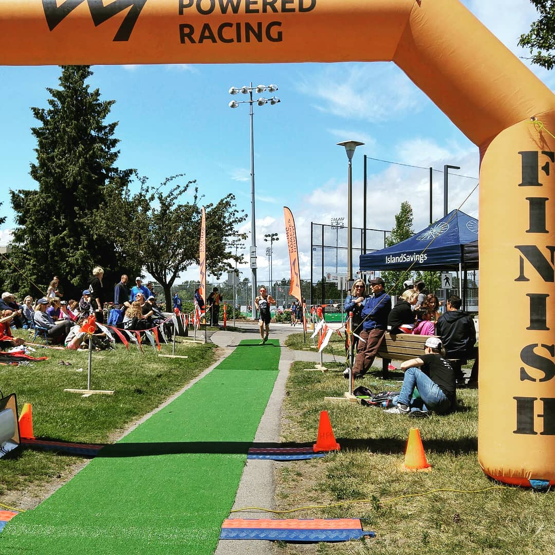 This is a photo of an inflatable orange archway the says 'finish' on the right side. There is a long false grass aisle with a racer in the distance running along it towards the finish line.