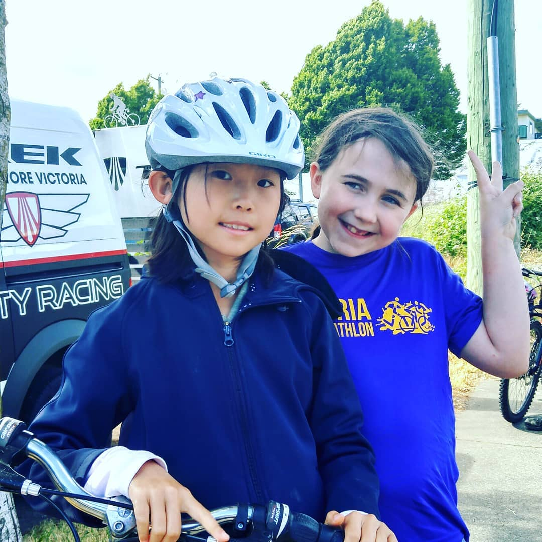 This is a photo of two young girls smiling at the camera. They are outside and the one in the front is on a bike with a white helmet. The other is smiling behind her and making a peace sign with her left hand.