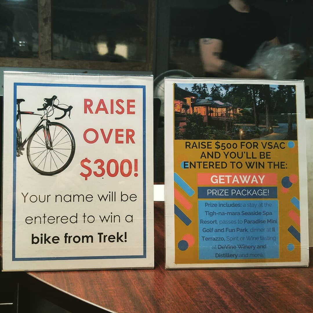 "This is a photo of two signs: one says ""raise over 300 dollars"" for a chance to win a bike from Trek, and the other says ""raise over 500 dollars"" for a chance to win a get away."