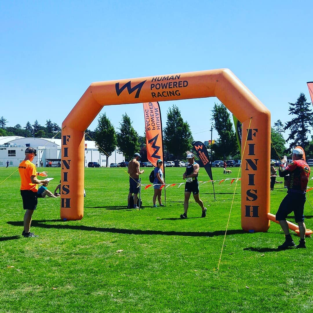 "An orange inflatable archway finish and start line marker that says ""Human Powered Racing"" on it with their logo, which is a jagged line shaped like a mountain range silhouette. There is a man in an orange tshirt on one side with the clipboard, and man in a black triathlon bodysuit walking through and others milling about around it. It is on a green grass field with a clear blue sky and trees in the background."