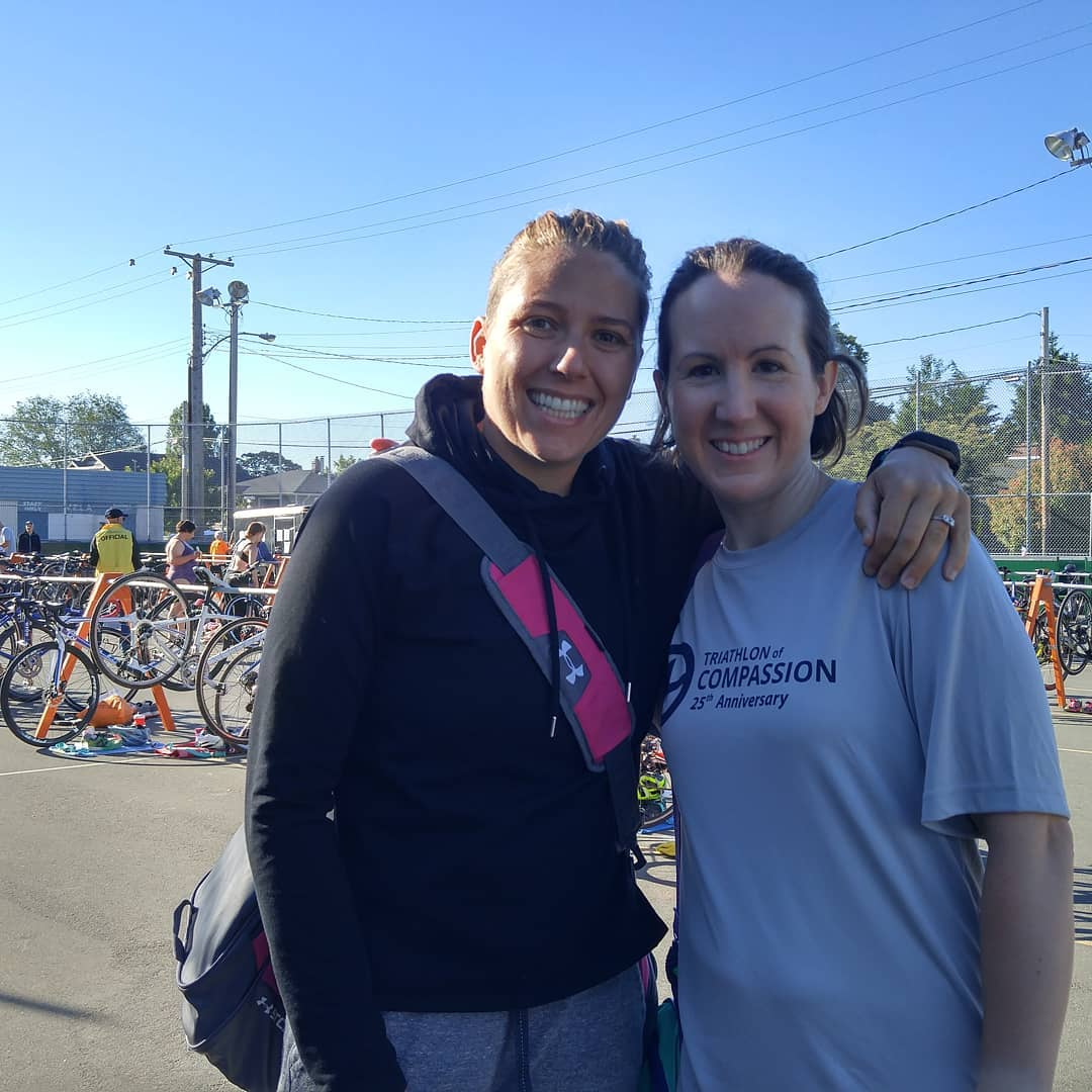 Two women in a makeshift bike parking lot. They are smiling with their arms around each other, and it is a sunny day.