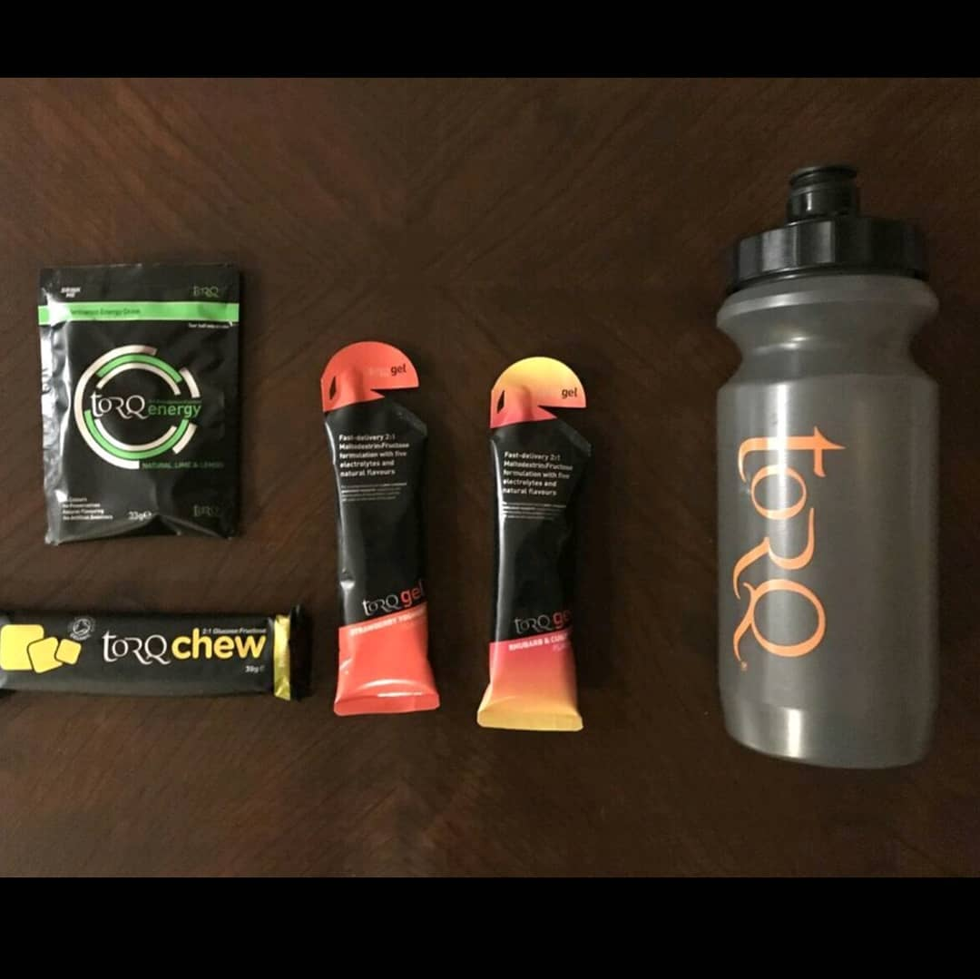 "Laid out on a wooden table from right to left: A clear plastic water bottle with a black lid that says ""TORQ"", two black and orange gel packets, and a ""TORQ Energy Packet"" above a ""TORQ"" energy bar."