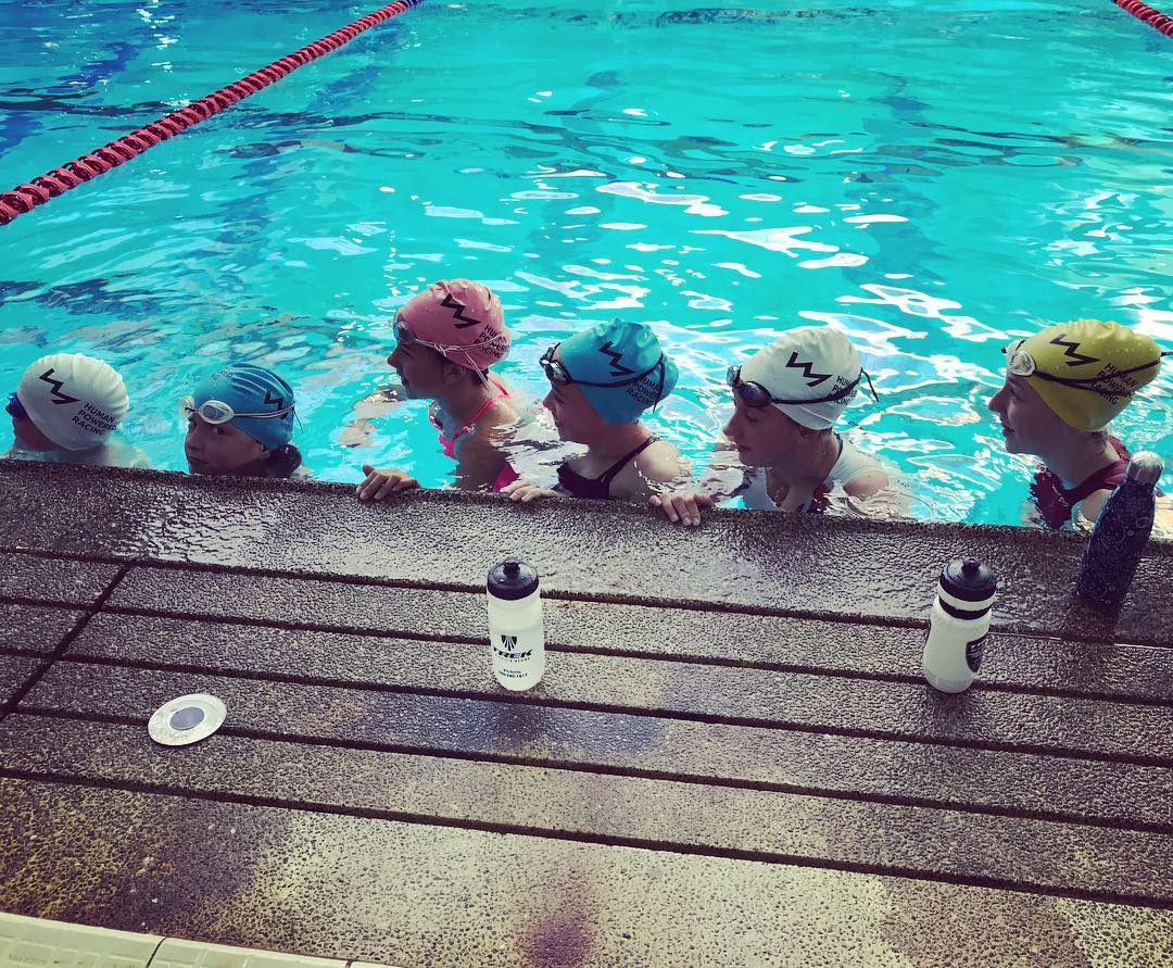 Five young people along the wall of the pool treading water. They are looking to the left and wearing swim caps and goggles.