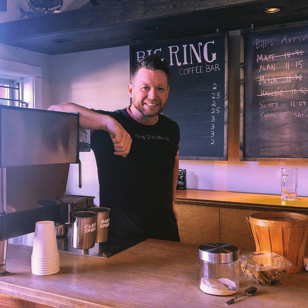 "This is a photo of a man in a black tshirt leaning against a metal espresso machine and standing behind a counter. There are chalk boards in the background, one says ""Big Ring Coffee Bar"" and the other is less legible."