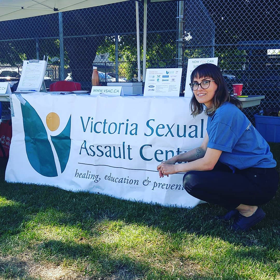 "A woman is kneeling to the right of a sign the is tied to a table and says ""Victoria Sexual Assault Centre."" She has brown hair, glasses, and is smiling at the camera. She is wearing a blue tshirt and black pants."