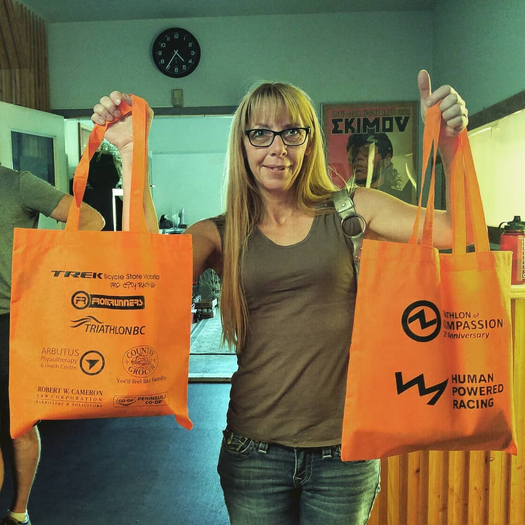 This is a photo of a woman indoors with long blonde hair and black glasses. She is smiling and holding up two matching orange shopping bags with the HPR logo - a black line in the shape of a mountain range - and other sponsor logos on them