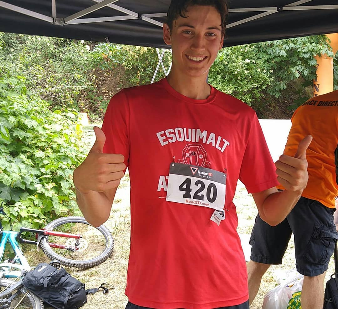 "This is a photo of a man smiling in a red shirt giving a double thumbs up (with both hands). His shirt says ""Esquimalt"" and he is standing under a black tent. His number is ""420."""