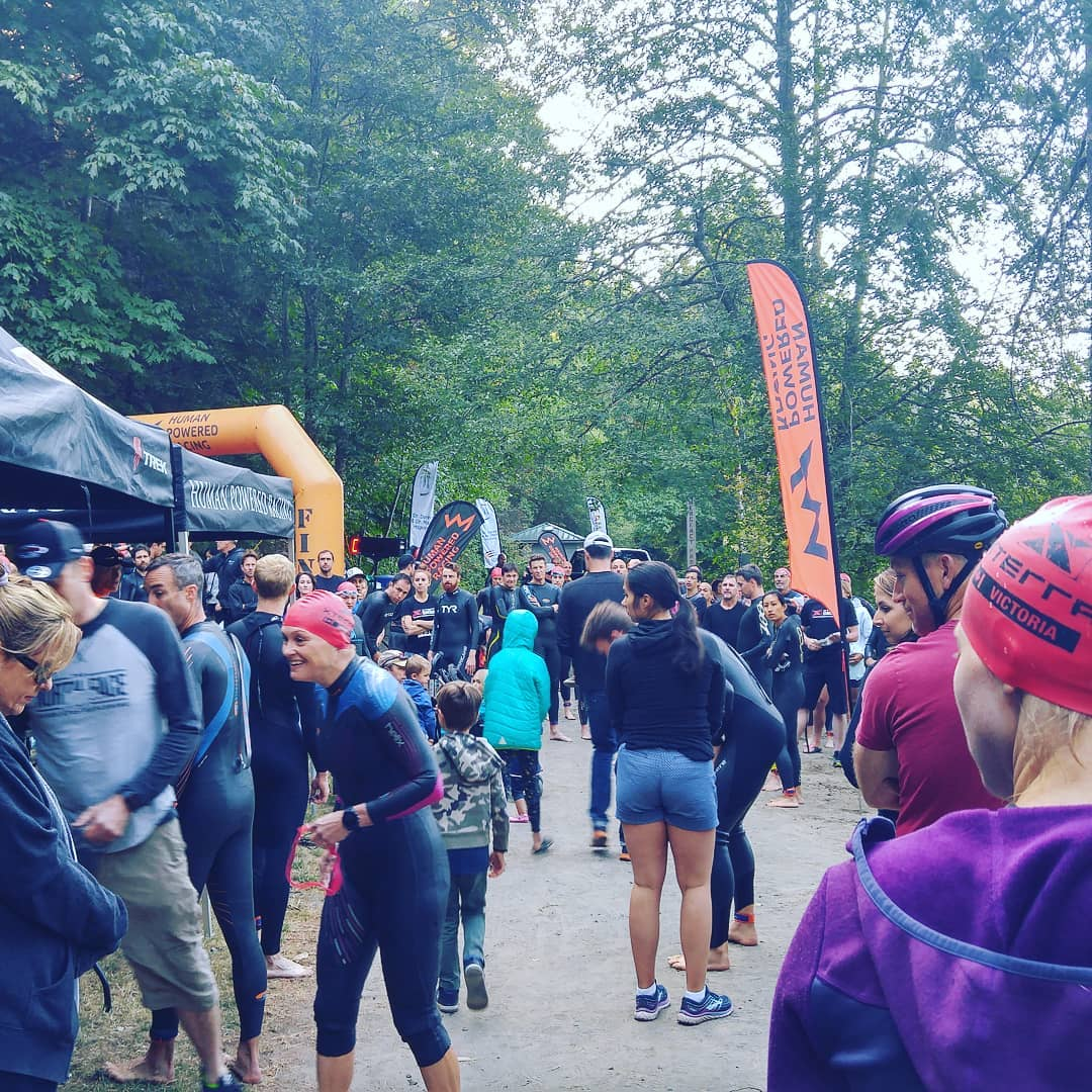 This is a photo of a crown. Most people are in triathlon gear with swim caps and goggles and body suits. It is a grey day and there are trees and orange markers in the background.