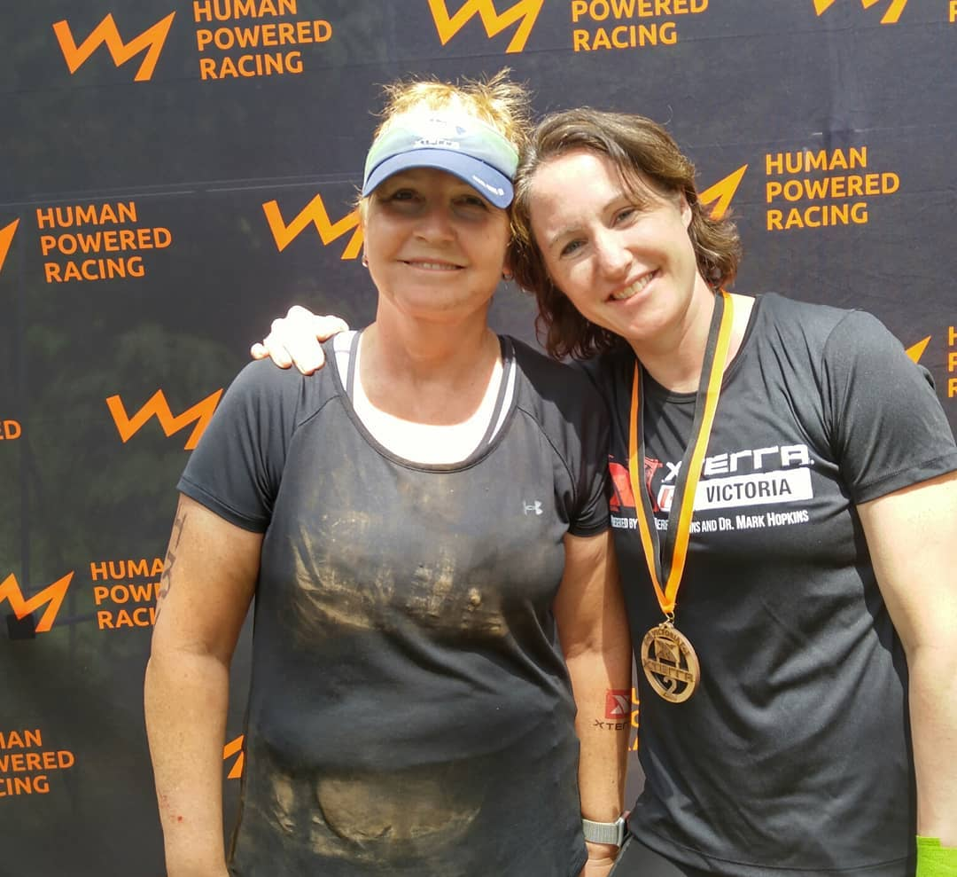 Two women who are quite muddy are smiling with their arms around each other, one with a metal, and in front of the black backdrop with the HPR logo on it, which is an orange line shaped like a mountain range silhouette