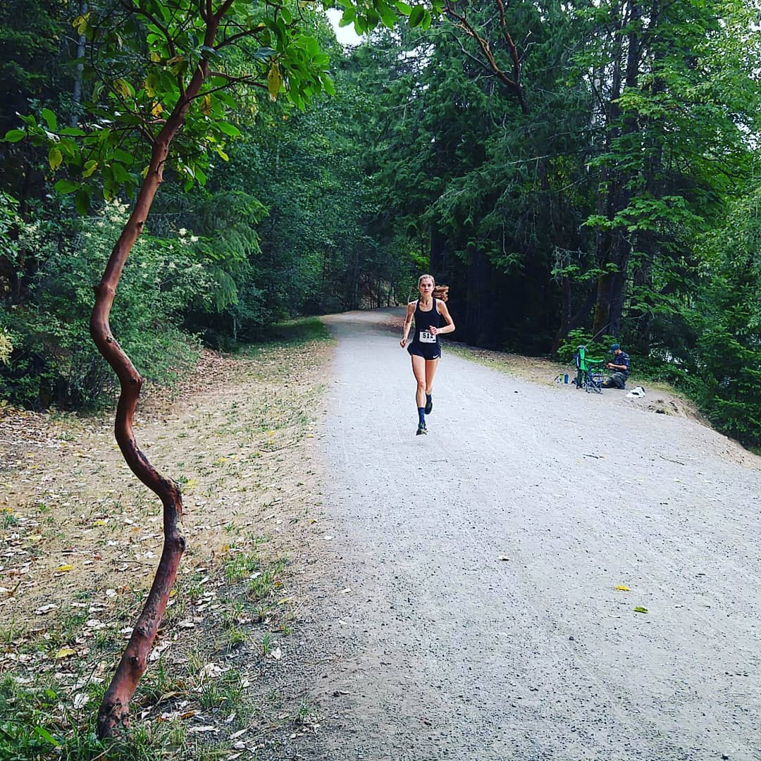 This is a photo of a woman running up a gravel road with evergreen trees on either side.