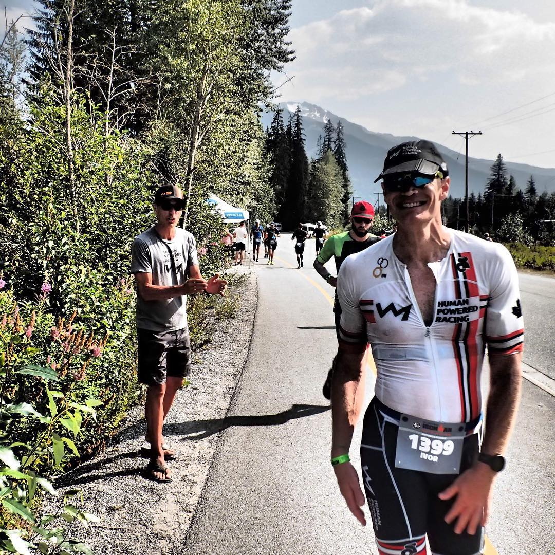 A man in a triathlon body suit and cap walking down the road and smiling. He is on the left of the road with trees beside him.